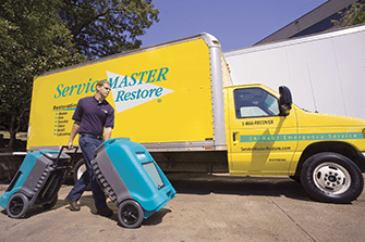 servicemaster van with man walking carrying two large blue equipments