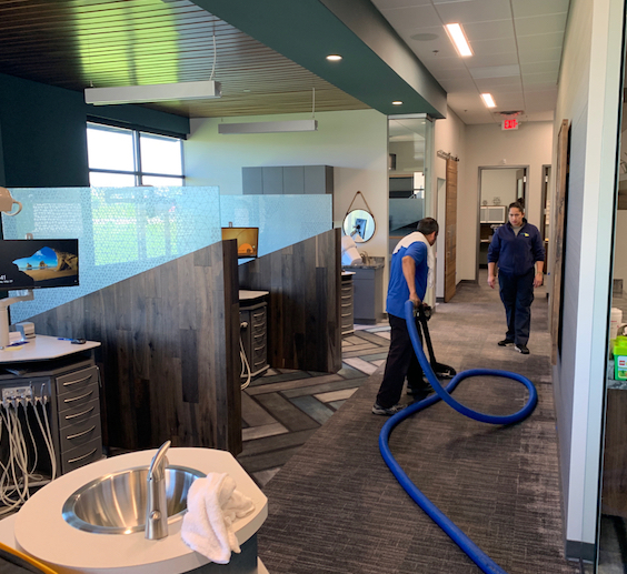 2 cleaners in blue shirt cleaning the floors at a modern office
