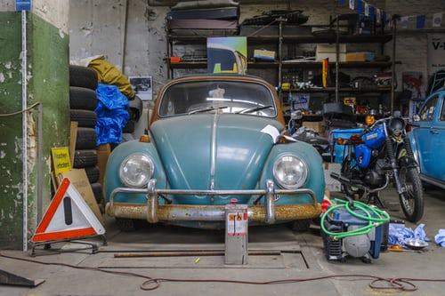 junk removed from a garage including an old vwbug and danger signs